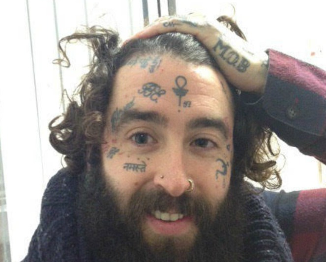 Male with facial tattoos and hand tattoos