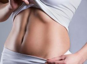 A lady's abdomen area in a grey background