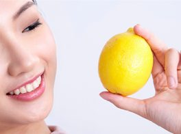 Asian lady holding a lemon