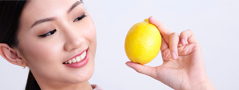 Asian lady holding a lemon