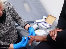 Lady getting finger pricked for food intolerance test