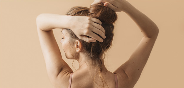 Lady putting hair in bun from behind