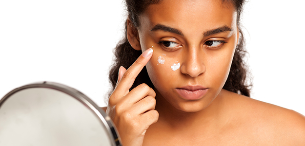 Lady applying cream to dark circles under eyes