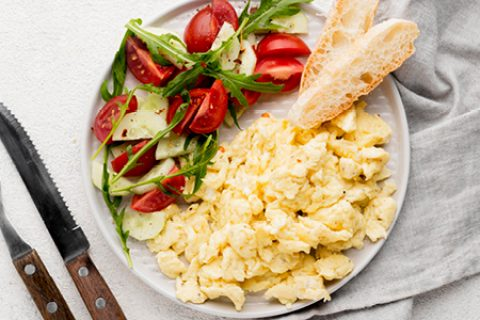 A breakfast dish with eggs, tomatoes, rocket and bread